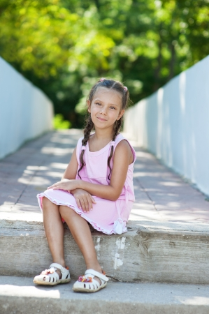 frock: Beautiful little girl with pigtails sitting on stone step, against background of summer city park.