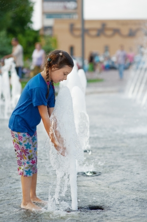Beautiful little girl playing with fountain in childrens city park. Stock Photo