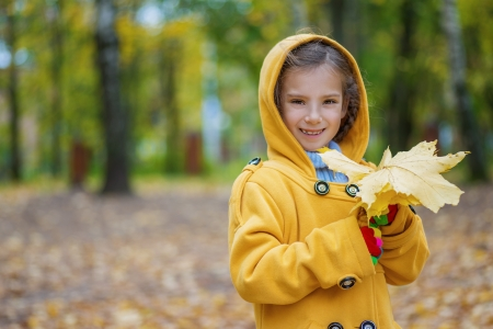 Portrait of beautiful smiling little girl in yellow hood with maple leaves in hands, against background of autumn park. Stock Photo - 15530328