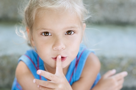 child finger: Beautiful little blonde girl with curly hair puts her finger to mouth, against background of summer city park.