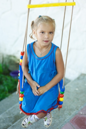 one child only: Portrait of beautiful little girl on swing in childrens city park. Stock Photo