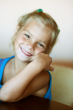 codo: Retrato de la hermosa niña divertida primer plano, sentado en la mesa.