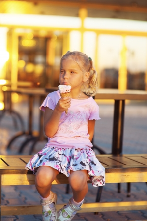 table skirt: Beautiful little girl sitting on bench and eating delicious ice cream.