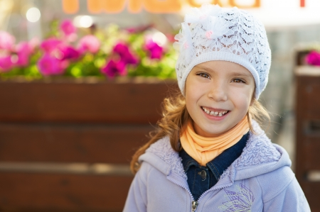 Beautiful funny little girl in jacket and hat, against background of growing flowers Stock Photo - 15637485