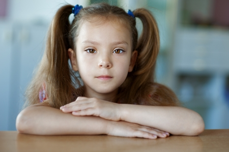Portrait of beautiful little girl close-up, sitting on table  Stock Photo - 15637488