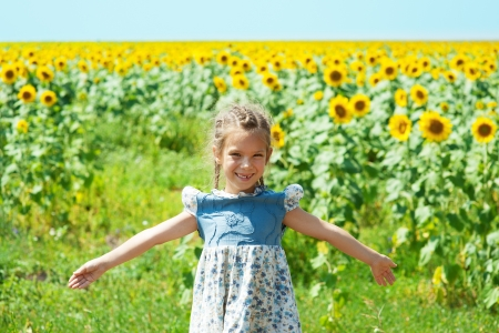 Portrait of beautiful smiling little girl, against background of sunflower field  Stock Photo - 15637487
