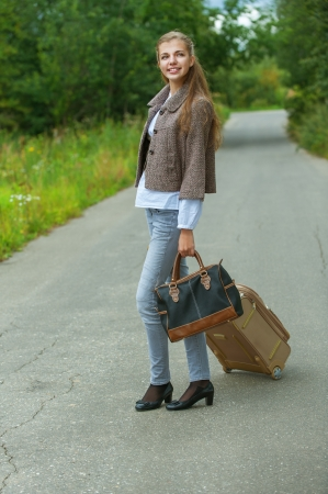 Portrait of smiling beautiful young woman with road suitcase, against background of autumn park. photo