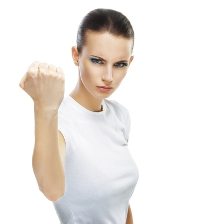 gruff: Beautiful sad young woman close-up threatens fist into camera, isolated on white background.