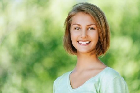 Portrait of smiling beautiful young woman close up, against background of summer green park. Stock Photo