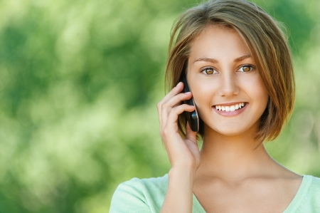 Portrait of smiling beautiful young woman close up with mobile phone, against background of summer green park. photo