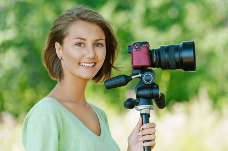 Portrait of smiling beautiful young woman close up with camera, against background of summer green park. photo