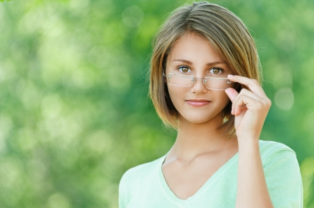 spec: Portrait of smiling beautiful young woman close up with glasses, against background of summer green park.
