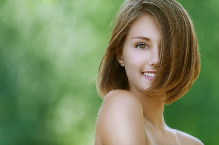nice day: Portrait of smiling beautiful young woman close up, against background of summer green park. Stock Photo