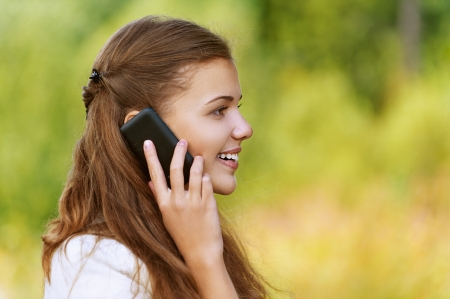 Young smiling pretty woman talking on mobile phone profile, against background of autumn park. photo
