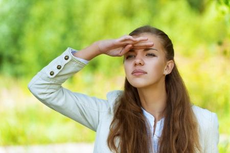 lejos: Mujer hermosa joven que mira en la distancia, contra el fondo de parque otoño.