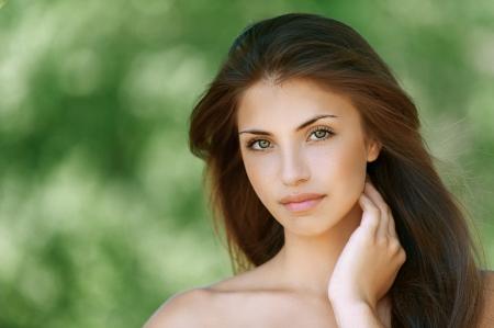 quiet adult: Ritratto di bella donna bruna giovane, su sfondo di parco verde di estate.