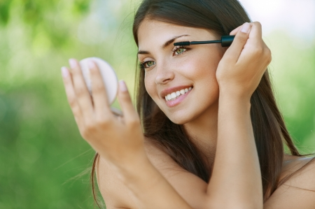 make up eyes: Pretty dark-haired funny young woman dyes her eyelashes, against background of summer green park.
