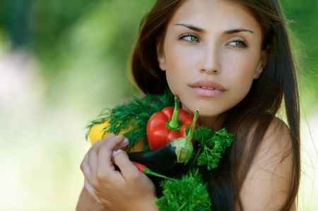 Beautiful dark-haired sad young woman holding vegetables - eggplant, peppers and parsley, against background of summer green park. Stock Photo - 15812512