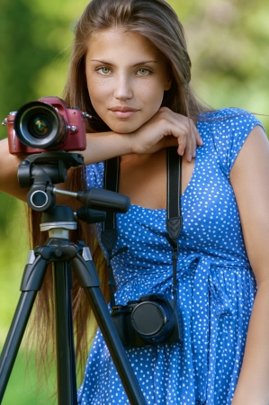 Mooie donkerharige kalme jonge vrouw met camera op statief, tegen de achtergrond van de zomer groen park.