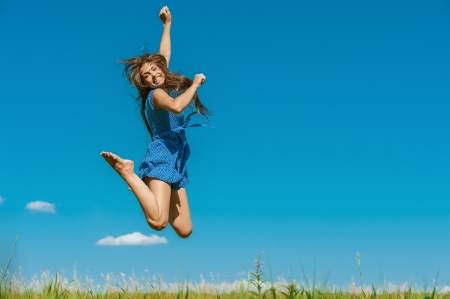 skip: Beautiful dark-haired happy young woman jumping high in air, against background of summer blue sky. Stock Photo