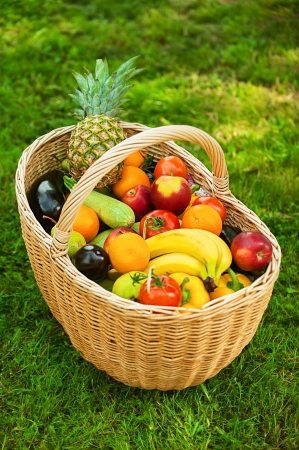 Large wicker basket with fruits and vegetables is on green grass. photo