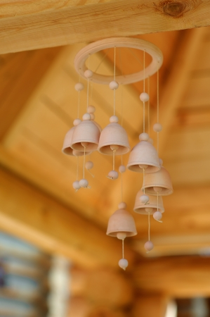 Traditional Russian wooden bells are suspended under roof. photo