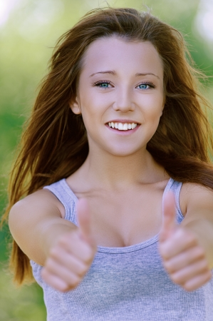 Pretty smiling young woman showing gesture that everything is OK, against background of summer green park. Stock Photo - 15891373