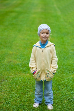 Beautiful little girl in yellow blouse and jeans standing on green lawn sheared Stock Photo - 16062249