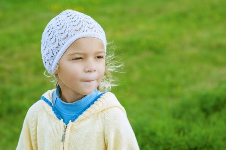 Beautiful little girl in yellow blouse close up on green lawn sheared  Stock Photo - 16062258