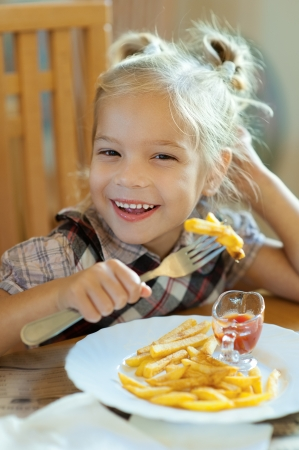 Beautiful laughing little girl sitting at table and eating French fries from your plate  photo