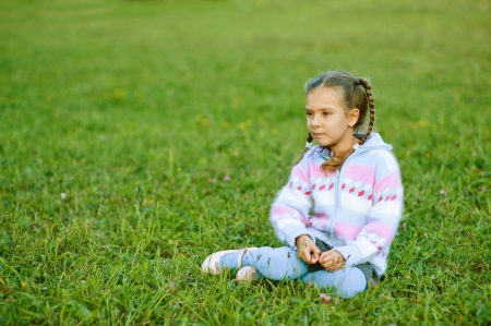 Little beautiful girl with pigtails sitting on green grass in summer city park  Stock Photo - 16062248