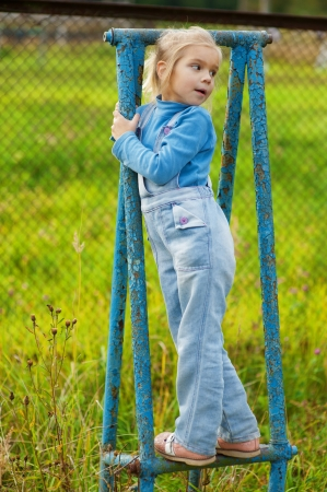Beautiful little girl in denim suit on rusty blue gymnastic apparatus  Stock Photo - 16062251