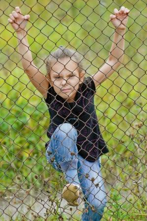 Little sad beautiful girl climbing on a metal grid Stock Photo - 16062250
