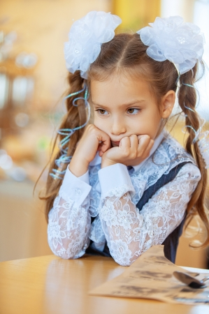 pigtails: Little sad girl with beautiful bows sitting at wooden table  Stock Photo