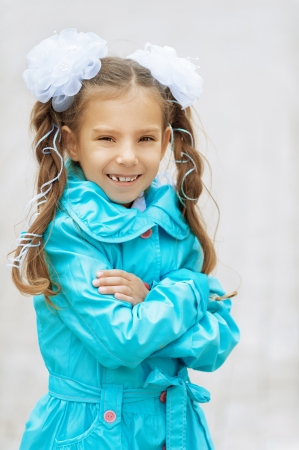 Little smiling beautiful girl with bows in blue cloak  Stock Photo - 16062259