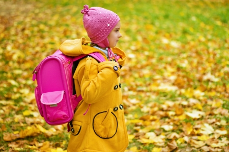 Little beautiful girl in yellow coat and pink backpack goes to school in autumn park  Stock Photo - 16062255