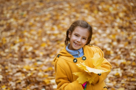 Little smiling beautiful girl in yellow coat holding maple leaf in autumn park  photo