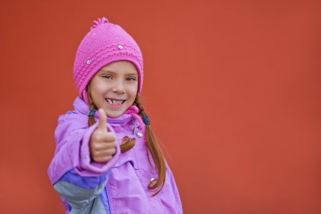 Little beautiful smiling girl in pink dress raises thumbs-up on red background Stock Photo - 16062256
