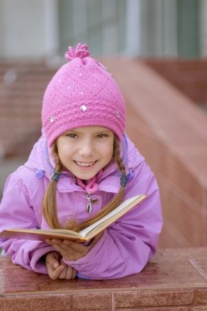 book jacket: Little beautiful smiling girl in pink dress reading book near school
