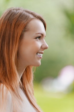 Portrait in profile of beautiful smiling young woman, against background of summer green park. photo