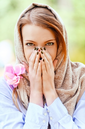 Beautiful young woman covered her hands, her face, against background of summer green park. photo