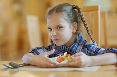 Beautiful little girl does not want to share meal in restaurant. Stock Photo - 16367568