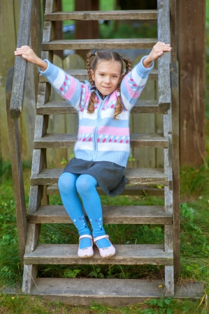 Beautiful little girl sitting on wooden stairs near playground in park. Stock Photo - 16367576
