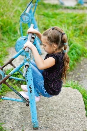 Beautiful little girl on old metal simulator around playground in park. Stock Photo - 16367585