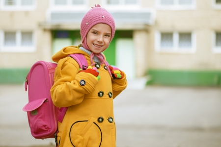 Beautiful smiling little girl in yellow coat with pink backpack goes to school. Stock Photo - 16351001