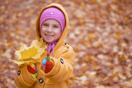 Pretty smiling little girl in yellow coat with pink cap collects yellow maple leaves in autumn city park. Stock Photo - 16367573