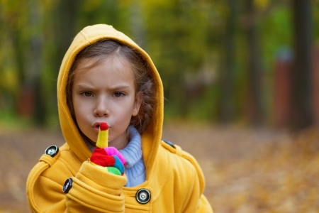Pretty sad little girl in yellow coat with hood put finger to lips in city autumn park. Stock Photo - 16367571