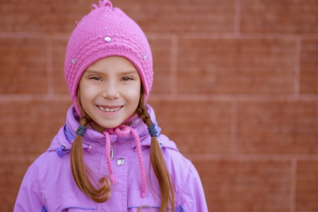 Portrait of smiling beautiful little girl in pink hat and jacket on red background of wall. Stock Photo - 16367570