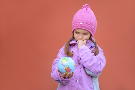 Beautiful sad little girl in pink coat holding globe and thinking on red background. Stock Photo - 16367569