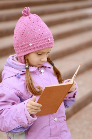 Beautiful little girl in pink coat reads orange book about stairs. Stock Photo - 16367586